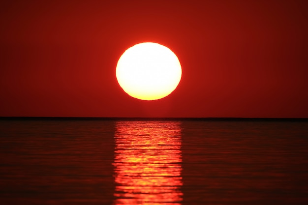 Long range shot of  sea reflecting the sun with the red sky Free Photo