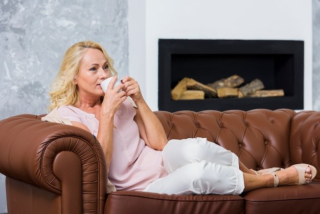 Long shot blonde lady drinking a cup of coffee Free Photo