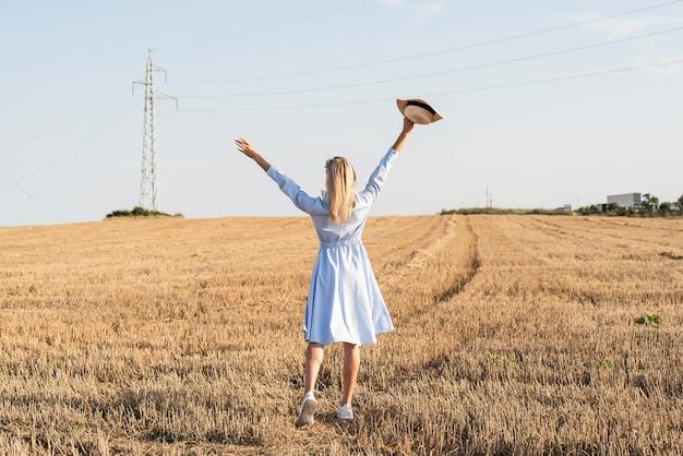 Длинный выстрел блондинка женщина, наслаждаясь природой в поле Бесплатные Фотографии