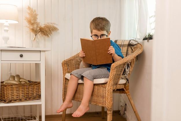 Мальчик с длинным выстрелом читает в кресле Бесплатные Фотографии