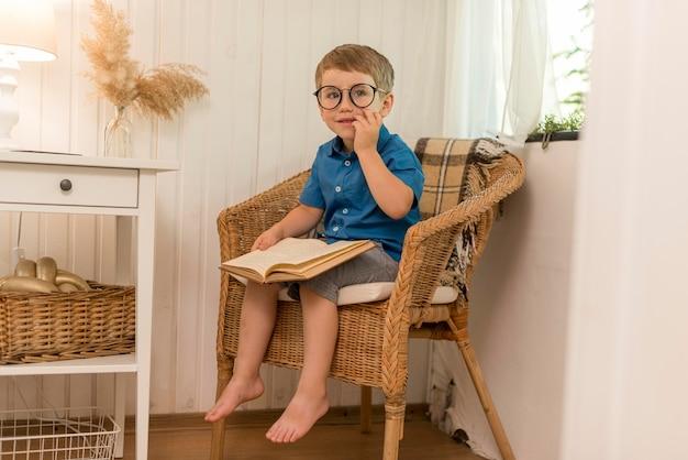 Мальчик с длинным выстрелом читает, сидя в кресле Бесплатные Фотографии