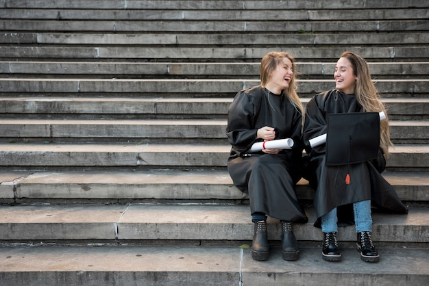 Long shot college friends laughing on stairs Premium Photo