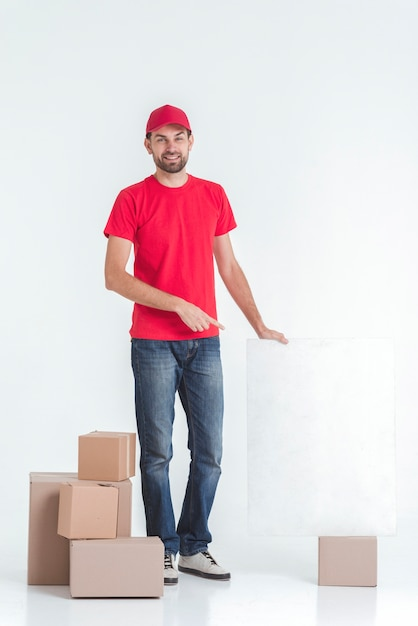 Long shot of courier surrounded by boxes Free Photo