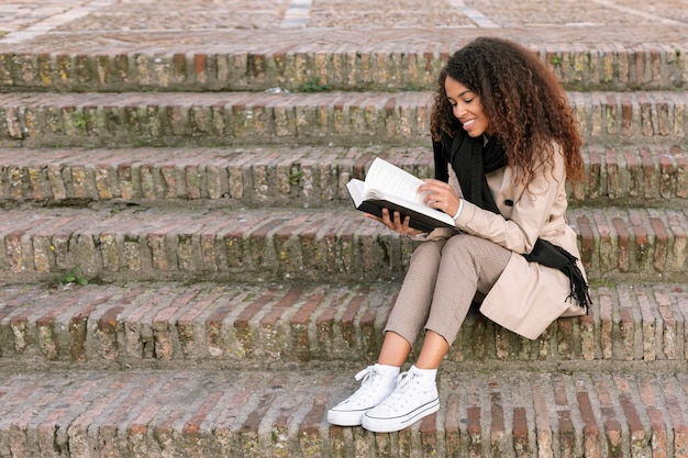 Long shot curly woman reading a book Free Photo