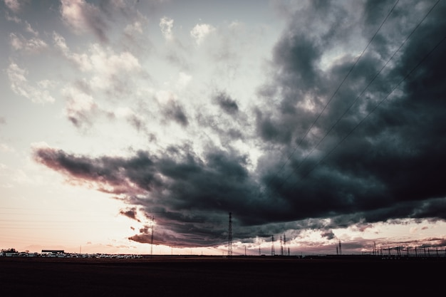 Long shot of a dark cloudy sky above antenna towers Free Photo