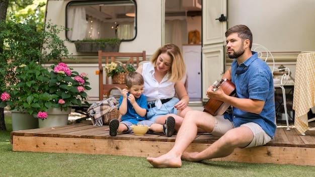 Long shot family enjoying some guitar music Free Photo