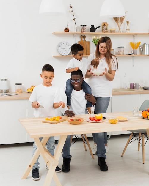 Long shot family having fun while making some food Free Photo