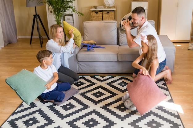 Длинный выстрел семья играет с подушками Бесплатные Фотографии