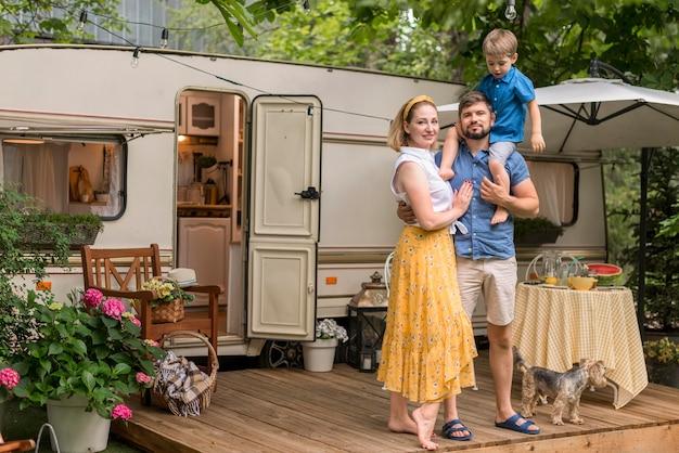 Семья с длинными снимками позирует рядом со своим караваном Бесплатные Фотографии