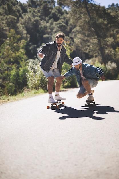 Long shot of friends skateboarding Free Photo