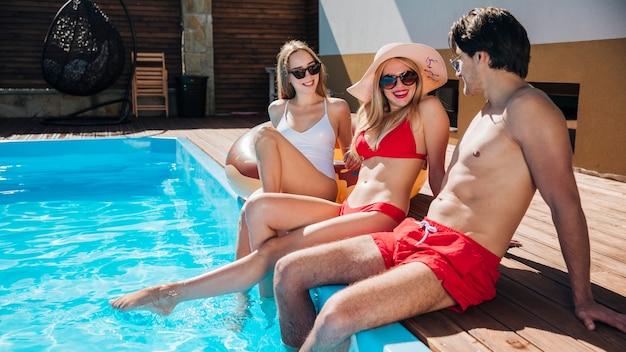 Long shot friends talking at the pool Free Photo