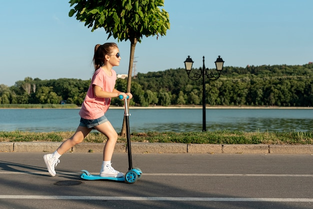Long shot of girl on blue scooter Free Photo