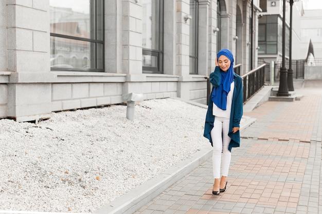 Long shot gorgeous girl with hijab smiling Free Photo