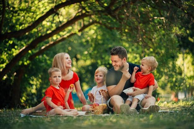 公園でロングショットの幸せな家族 Premium写真