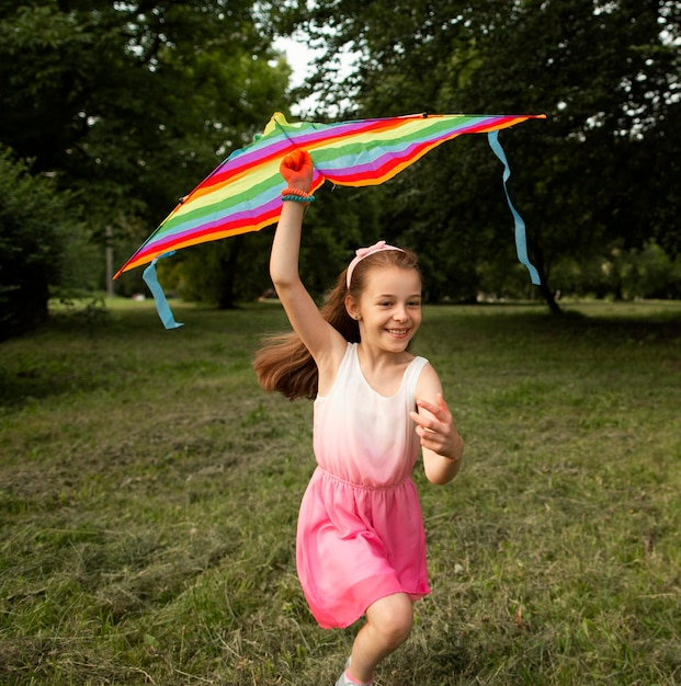 Long shot of happy girl having fun with a kite Free Photo