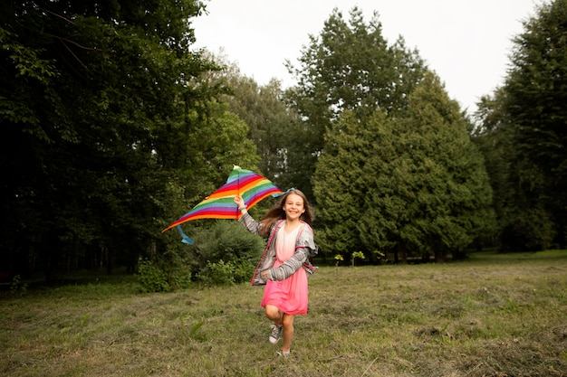 Long shot of happy girl having fun with a kite Free Photo