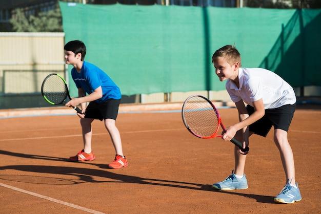 Long shot kids playing double tennis Free Photo