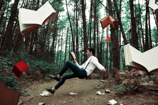 Long shot levitating man reading in the forest Free Photo