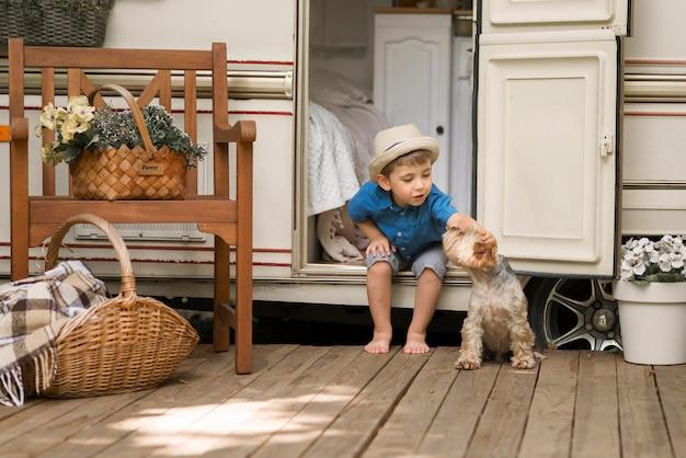 Длинный выстрел маленький мальчик сидит в караване рядом с милой собакой Бесплатные Фотографии
