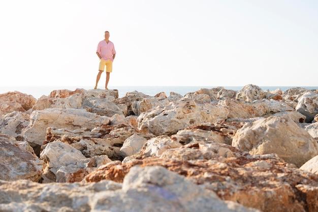 Длинный выстрел человек позирует на скалах Бесплатные Фотографии