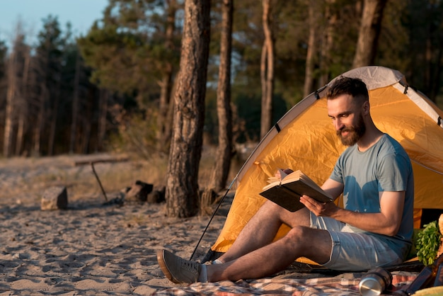 Long shot of man reading a book by the tent Free Photo
