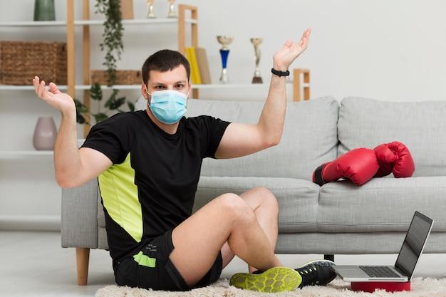 ロングショットの男性が医療用マスクを着用しながらトレーニング 無料写真