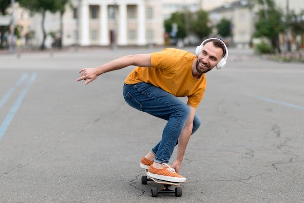 Colpo lungo dell'uomo con lo skateboard Foto Gratuite