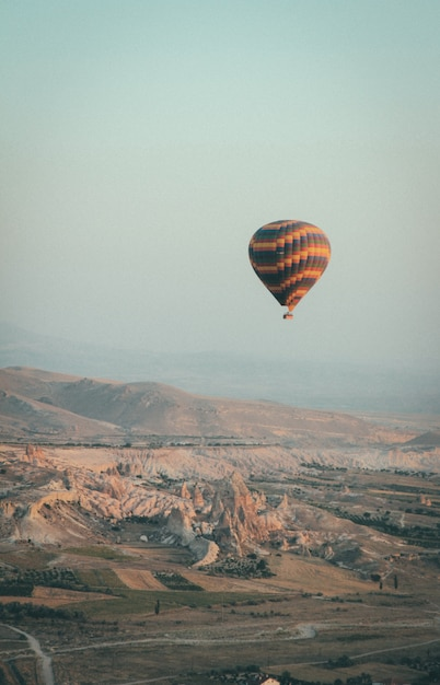 Long shot of a multi-colored hot air balloon floating in the sky high above mountains Free Photo