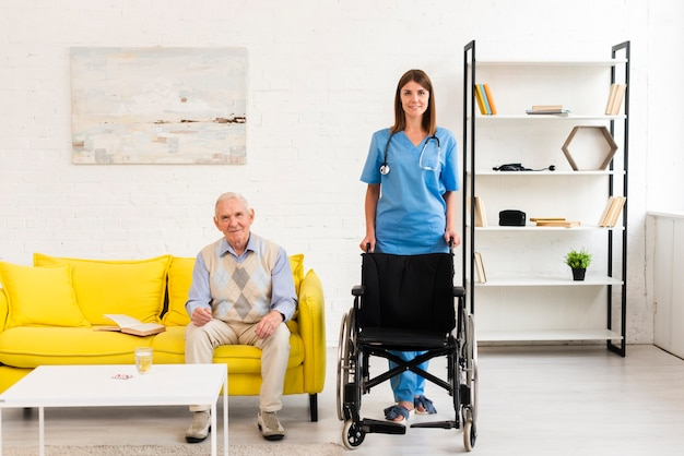 Long shot nurse holding a wheelchair for old man Free Photo