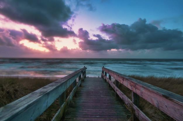 Длинный снимок променада, ведущего к пляжу с красочным закатом, в веннингштедте, зильт, германия Бесплатные Фотографии