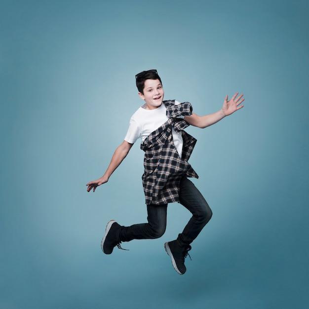 Длинный выстрел мальчика прыгает и позирует Бесплатные Фотографии
