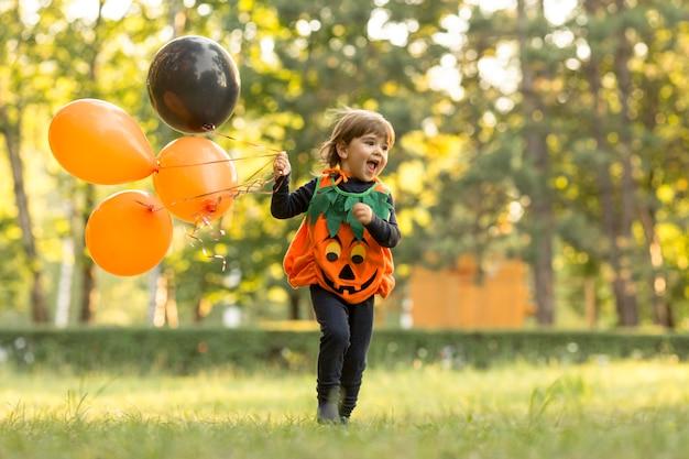 Длинный снимок милого маленького мальчика в костюме тыквы Бесплатные Фотографии