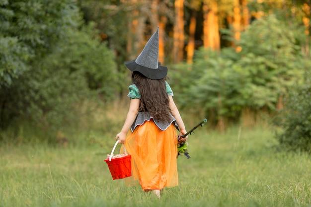 Длинный снимок девушки в костюме ведьмы на хэллоуин на природе Бесплатные Фотографии