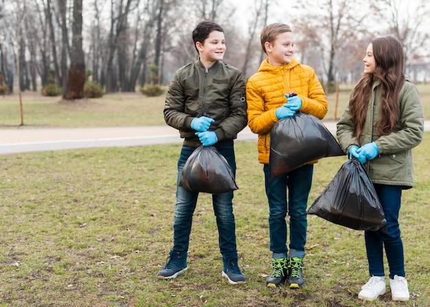 ビニール袋を保持している子供のロングショット 無料写真