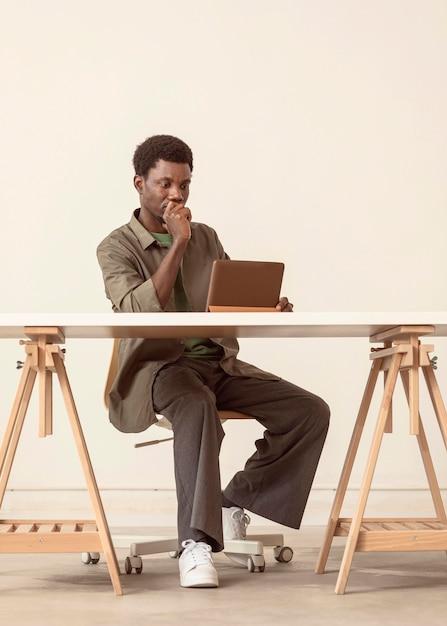 座ってラップトップで作業している人のロングショット 無料写真