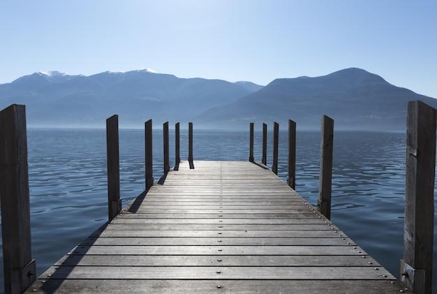 Длинный снимок доков, простирающихся к озеру, с горами на горизонте. Бесплатные Фотографии