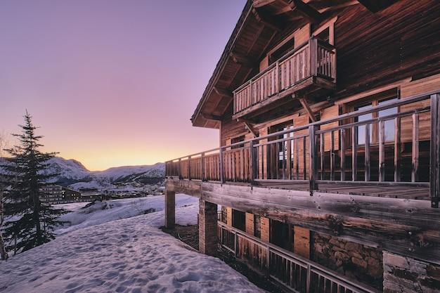 일출 동안 프랑스 알프스의 Alpe D Huez 스키 리조트에있는 오두막의 외관의 긴 샷 무료 사진