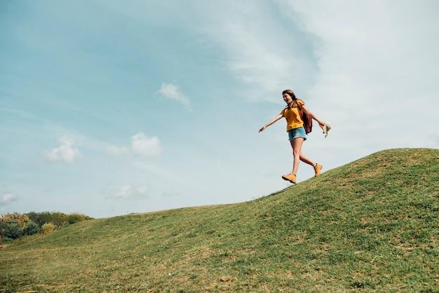 丘を下る女性のロングショット 無料写真