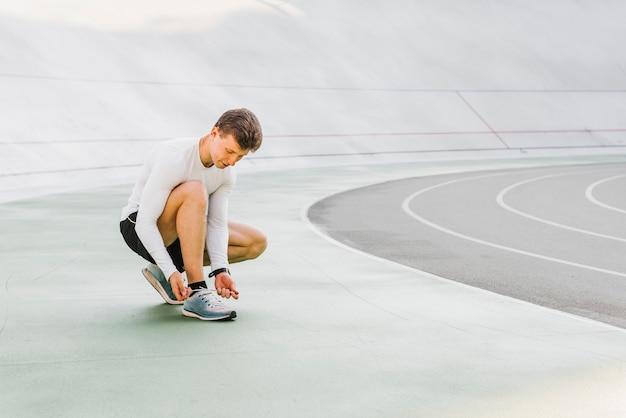 Long shot of runner tying his shoes Free Photo
