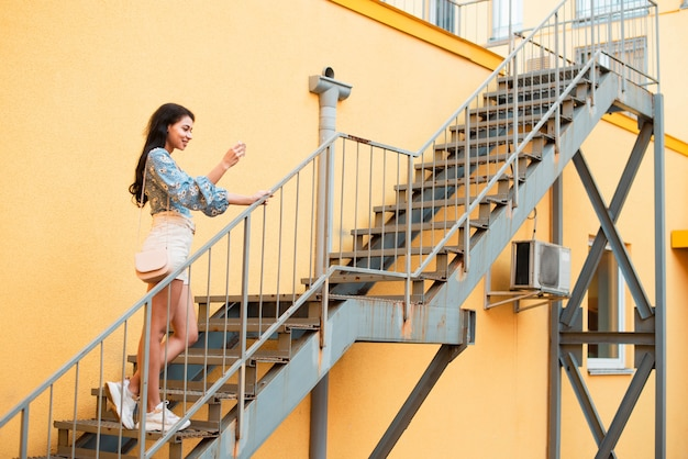 Long shot of sideways woman standing on stairs and taking photos Free Photo