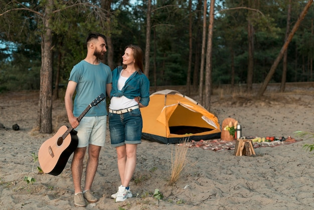 Long shot standing couple next to tent Free Photo
