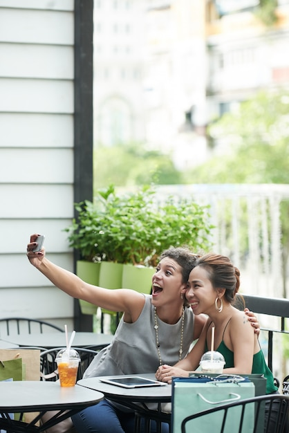 Long shot of two girls taking funny selfie in a summer cafe Free Photo