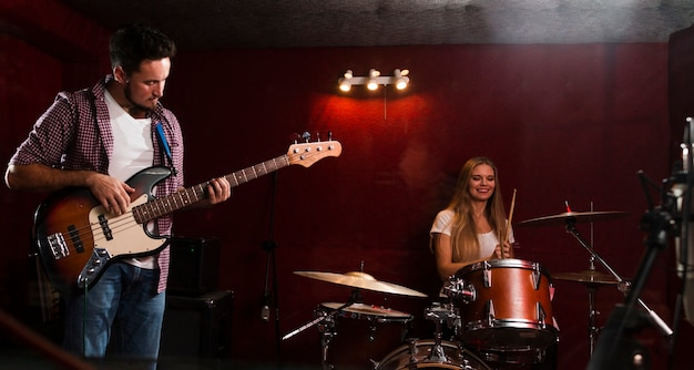 Long shot view of woman playing drums and man playing guitar Free Photo