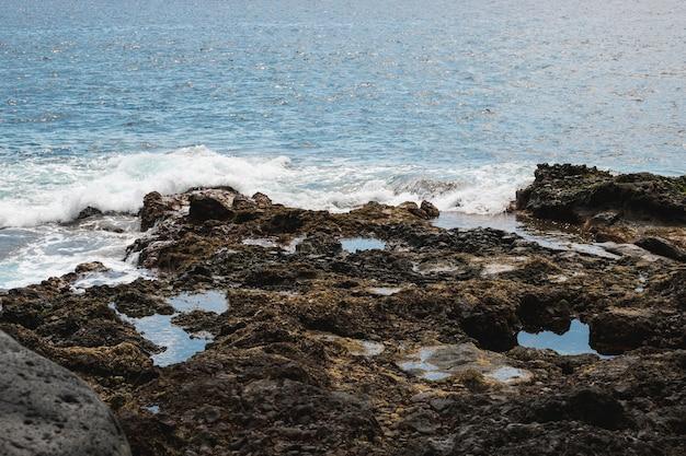 Long shot wavy water at rocky shore Free Photo