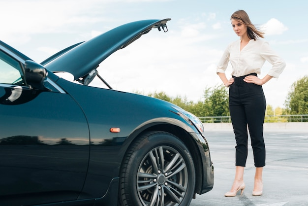 Long shot of woman and car Free Photo