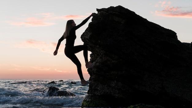 Long shot woman climbing a rock next to the ocean Free Photo
