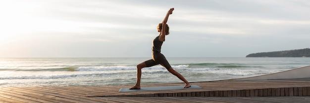 Длинный выстрел женщина делает позу воина на пляже Premium Фотографии