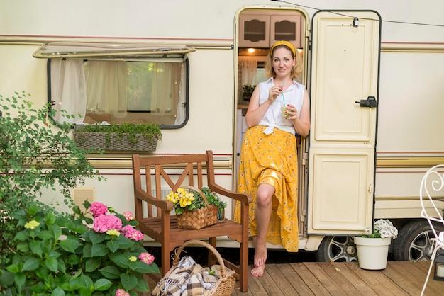 Длинный выстрел женщина, держащая стакан лимонада рядом с караваном Бесплатные Фотографии