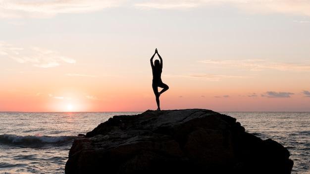 Длинный выстрел женщина в спортивной одежде медитирует на скале Premium Фотографии