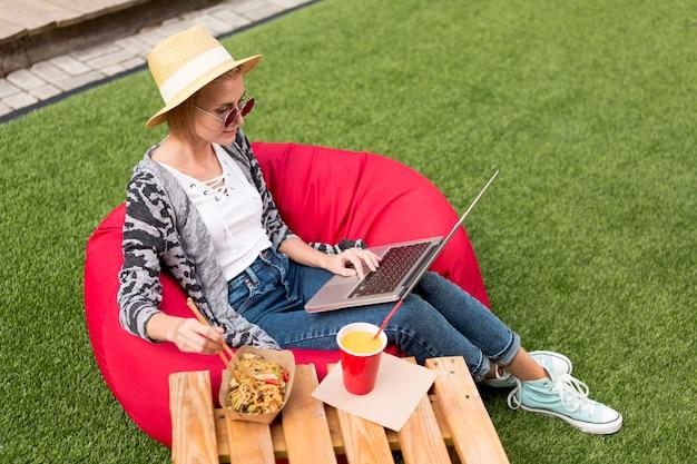 Long shot of woman looking at laptop Free Photo